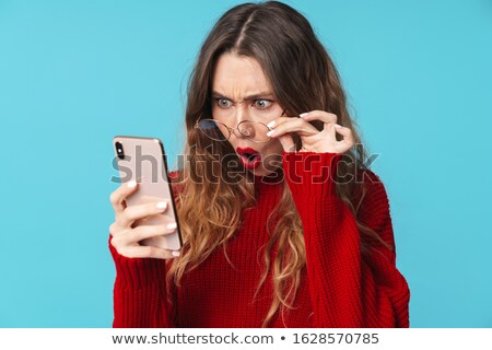 Image of displeased nice woman using cellphone and expressing surprise Stock photo © deandrobot