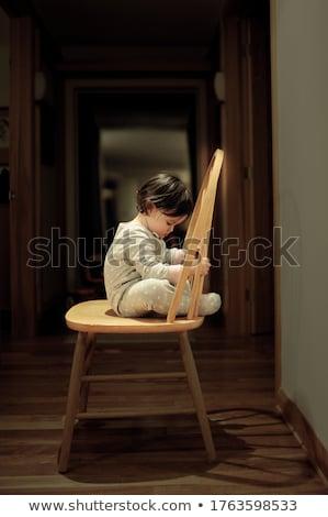 Sad woman sitting on a chair Stock photo © konradbak