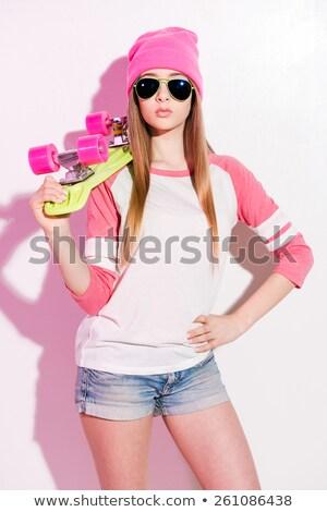 Woman standing holding sunglasses against white background Stock photo © wavebreak_media