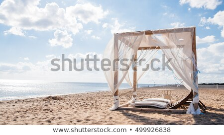 Lounge chairs with a sun canopy on the beach. Stock photo © borysshevchuk