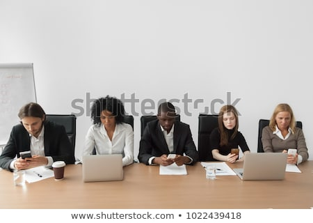 Businesswoman text messaging with colleagues using laptop behind Stock photo © wavebreak_media