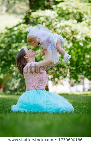 smiling little girl sits in grass with lifted hands Stock photo © Paha_L