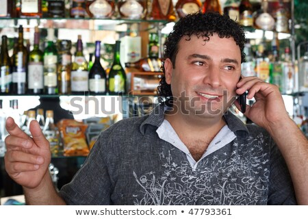 Barman talks by  Smiling man against shelves with bottles. Stock photo © Paha_L