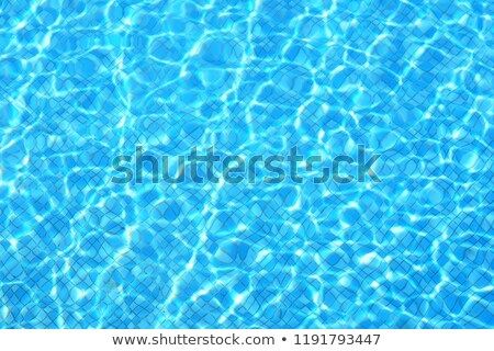 Blue ripped water in swimming pool with sun reflections Stock photo © Escander81