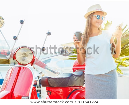 Stock photo: Trendy woman drinking takeaway coffee near her red moped on the