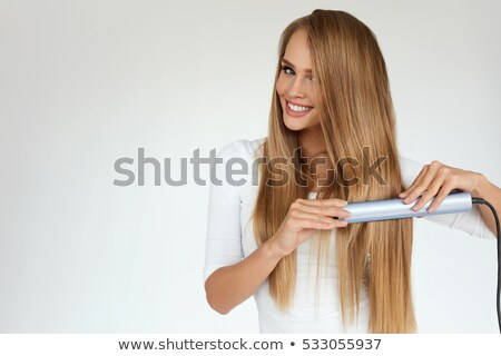 Woman hairdresser using straightener for long hair of young female  Stock photo © deandrobot