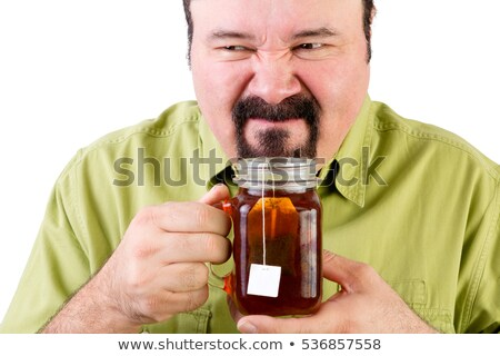 Man grimacing as he smells tea in a cup Stock photo © ozgur