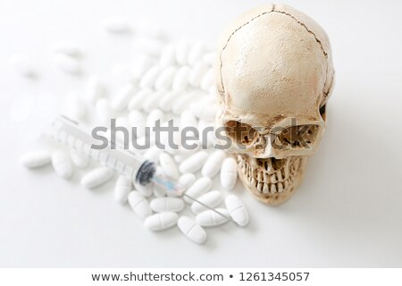 blurry skull and syringe stock photo © klinker