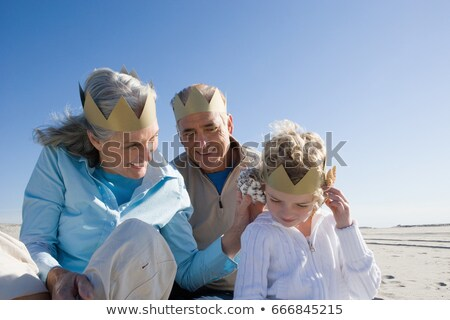 Grandparents and granddaughter wearing paper crowns on beach Stock photo © IS2