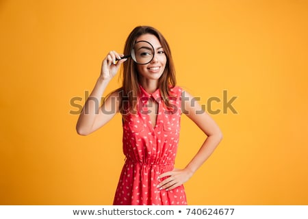 beautiful smiling woman with magnifying glass Stock photo © dolgachov