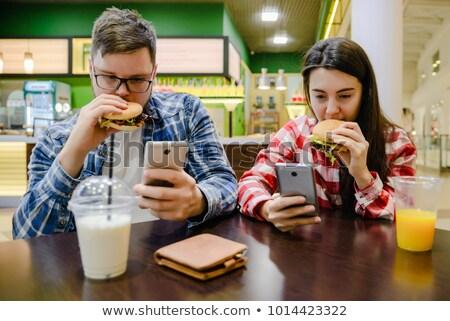 Homme parler téléphone portable manger Burger portrait Photo stock © AndreyPopov