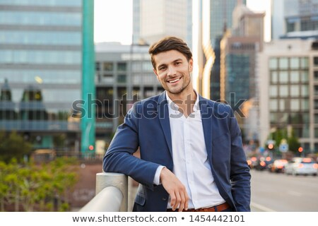 happy businessman dressed in shirt standing outdoors stock photo © deandrobot