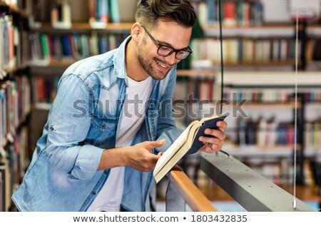Casual moço leitura livro sessão prateleira de livros Foto stock © pressmaster