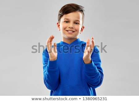 portrait of smiling boy in blue hoodie applauding Stock photo © dolgachov