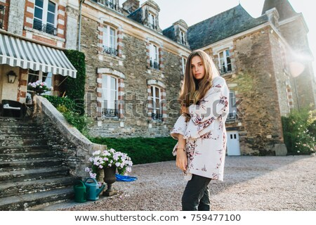 Good looking serious female model wears cape, poses against ancient castle, has excursion in old cit Stock photo © vkstudio