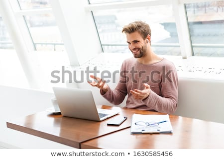 Image of young bearded handsome man wearing eyeglasses holding laptop Stock photo © deandrobot