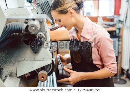 Woman cobbler working on machine in her shoemaker workshop Stock photo © Kzenon