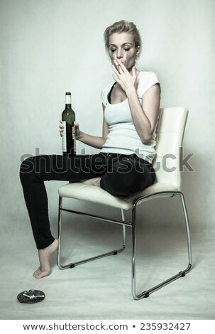 Sad blond woman with cigarette and botle of wine Stock photo © imarin