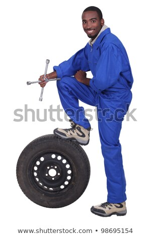 blue collar holding cross faucet with leg resting on pneumatic tyre stock photo © photography33