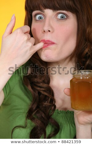 Woman dipping little finger in jar of honey Stock photo © photography33