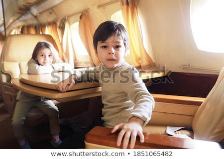 young boy is flying business class in the aircraft with his snug Stock photo © meinzahn
