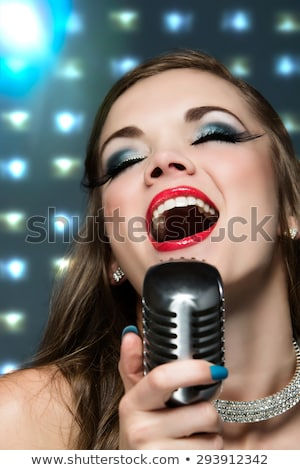 gorgeous woman in black dress holding microphone and singing stock photo © feelphotoart