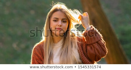 Blond Woman Playing with Strand of Hair Outdoors Stock photo © dash