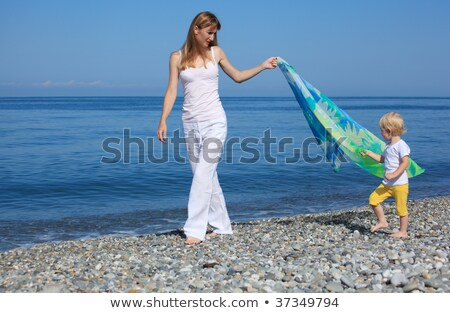 Mother and child with shawl walk on edge of sea Stock photo © Paha_L