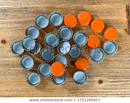 Large pile of beer bottle caps on wooden desk Stock photo © stevanovicigor