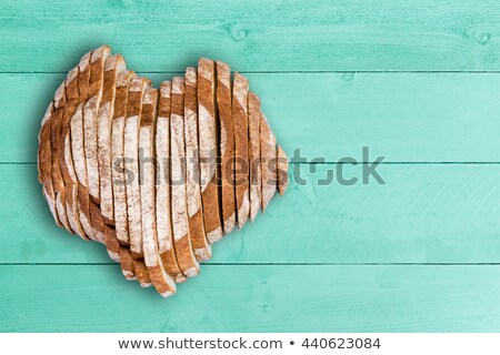 sliced bread loaf shaped as heart over green wood stock photo © ozgur