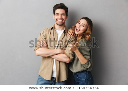 Young couple embracing over gray background Stock photo © julenochek