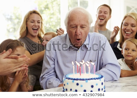 Grandfather blowing out candles at party Stock photo © IS2