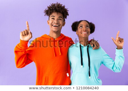Portrait of joyous african american guy smiling and pointing fin Stock photo © deandrobot
