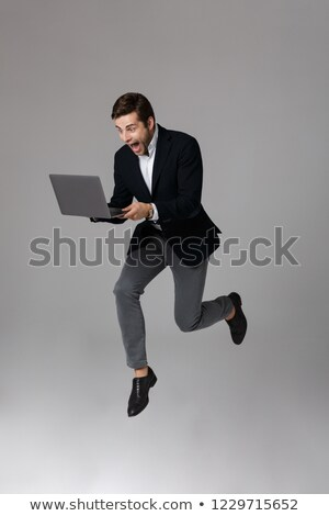 Full length image of joyous businessman 30s in suit rejoicing wh Stock photo © deandrobot