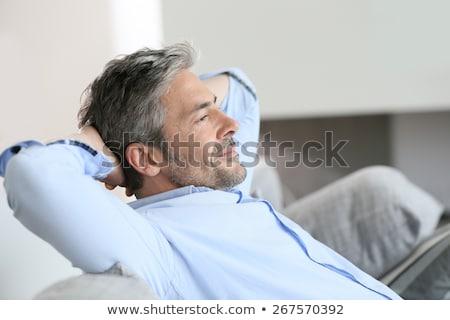 happy middle-aged man sitting on sofa at home Stock photo © dolgachov