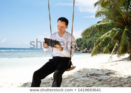 Adam oturma salıncak dijital tablet plaj Stok fotoğraf © AndreyPopov
