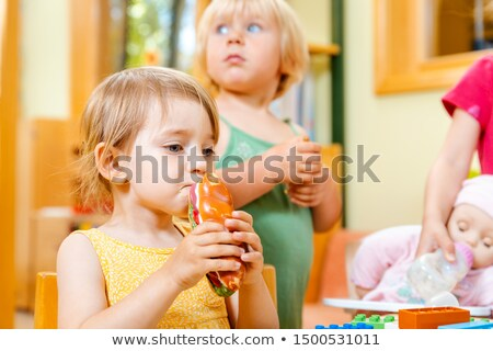 Children eating some food in play school Stock photo © Kzenon