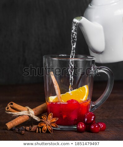 Glass transparent glass with cranberry drink with cinnamon and lemon isolated on a white background. Stock photo © Lady-Luck