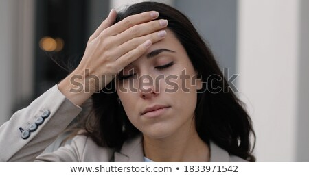 Portrait of a beautiful woman having a headache while standing against a white background stock photo © wavebreak_media