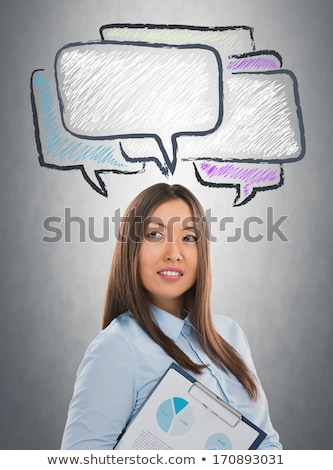 Portrait of pretty business woman looking at dialogue symbols ov Stock photo © hasloo