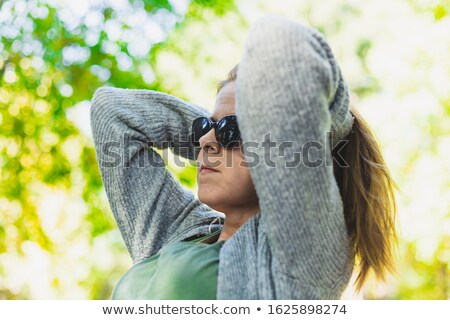 Seductive young woman with hands behind  head Stock photo © deandrobot