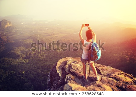 Hiking woman with backpack taking photo with smartphone Stock photo © blasbike