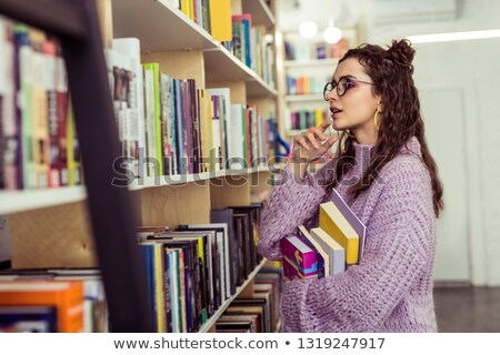 Сток-фото: Girl Choosing Books Between The Shelves In The Library