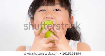 Cute black hair little girl eating green apple Stock photo © boggy