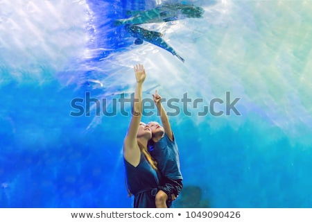 Mother and son looking at fish in a tunnel aquarium Stock photo © galitskaya