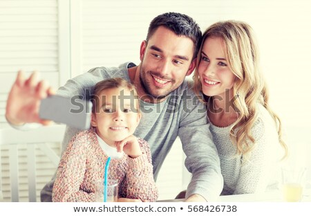 mother picturing father with baby by smartphone Stock photo © dolgachov