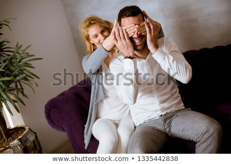 Pretty young woman covering mens eyes doing a surprise Stock photo © boggy