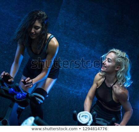 Nő biciklizik tornaterem mosolyog fiatal egészséges Stock fotó © Kzenon