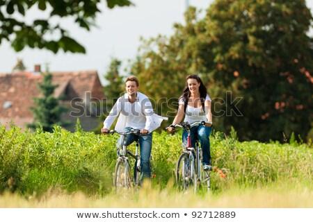 Boldog pár biciklik vidéki út emberek szabadidő Stock fotó © dolgachov