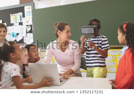 Front view of a Caucasian schoolboy using a virtual reality headset at desk in a classroom at school Stock photo © wavebreak_media